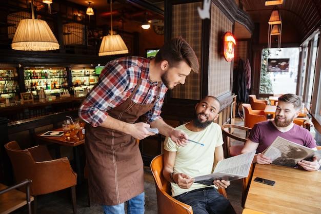 Sorridente giovane cameriere che dà consigli e aiuta a fare un ordine per due uomini al bar