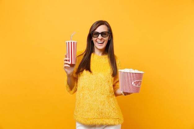 Sorridente giovane donna in occhiali 3d imax guardando film, tenendo secchio di popcorn, bicchiere di plastica di cola o soda isolato su sfondo giallo. persone sincere emozioni nel cinema, concetto di stile di vita.