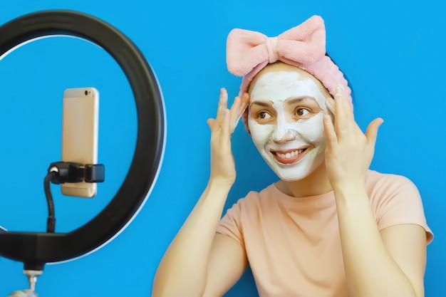 La giovane donna sorridente applica una maschera cosmetica di crema sul viso e trasmette online sul suo smartphone nei social network con i suoi follower