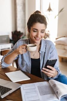Sorridente giovane donna in abbigliamento casual utilizzando il telefono cellulare e il laptop mentre studiava al coperto