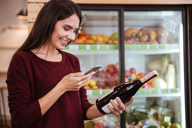 Sorridente giovane donna che sceglie la vite e scansiona il codice a barre sulla bottiglia nel negozio di alimentari