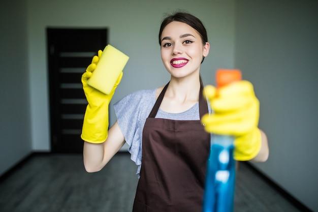 La giovane donna sorridente pulisce la finestra con lo straccio