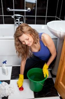 La giovane donna sorridente che pulisce il pavimento del bagno