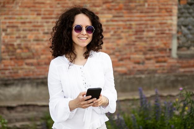 Sorridente giovane donna close-up ritratto vestito di bianco, guardando la telecamera, in possesso di un telefono cellulare, contro un edificio con sfondo di mattoni rossi.