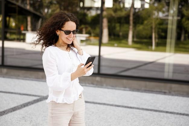 Sorridente giovane donna, ritratto del primo piano, guardando il telefono cellulare, contro un edificio con sfondo della finestra.