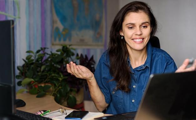 Giovane donna sorridente in camicia di jeans che lavora a casa vicino al computer portatile