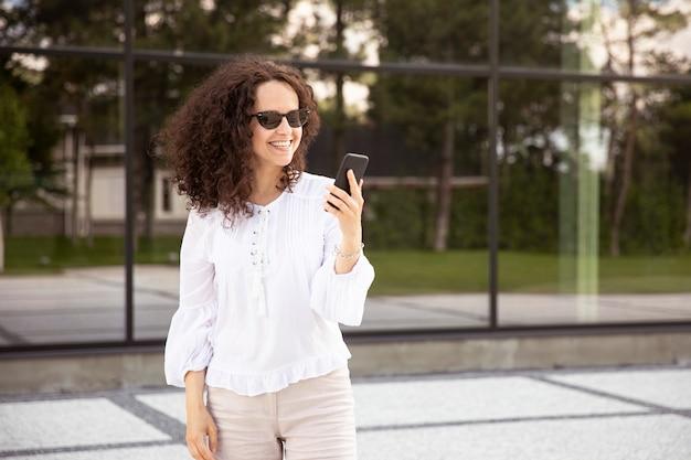Sorridente giovane donna vestita di bianco, guardando il telefono cellulare, contro un edificio con sfondo della finestra.