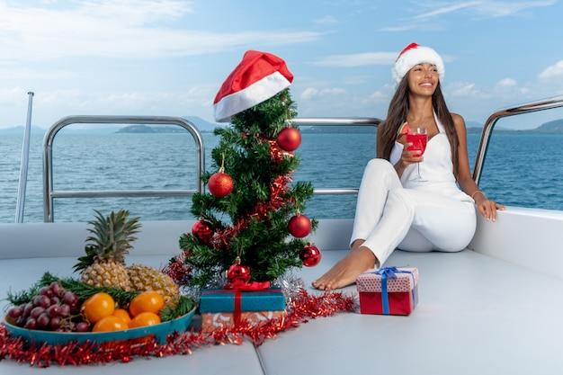 Sorridente giovane donna che beve bevande e mangia frutta tropicale per natale durante una crociera in yacht. natale e capodanno
