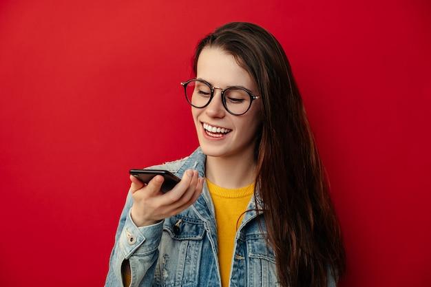 La giovane donna sorridente in occhiali che tengono il telefono parla attiva l'assistente virtuale virtuale di riconoscimento vocale sullo smartphone, messaggio felice del record di assistenza di internet di comando della ragazza, concetto della tecnologia