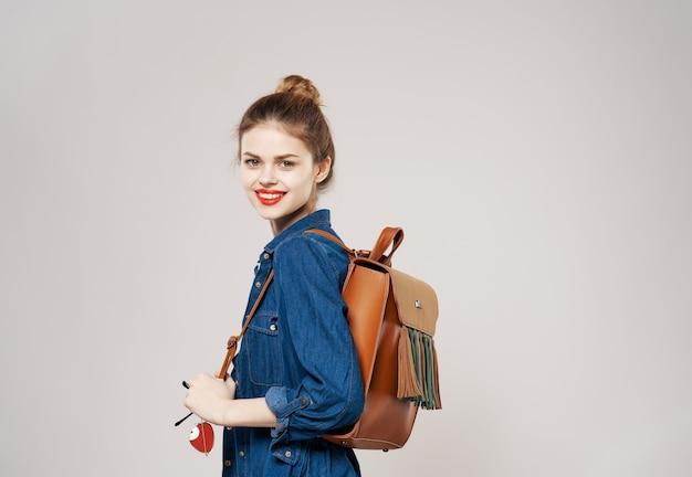 Sorridente giovane donna vestiti di moda zaino studente college