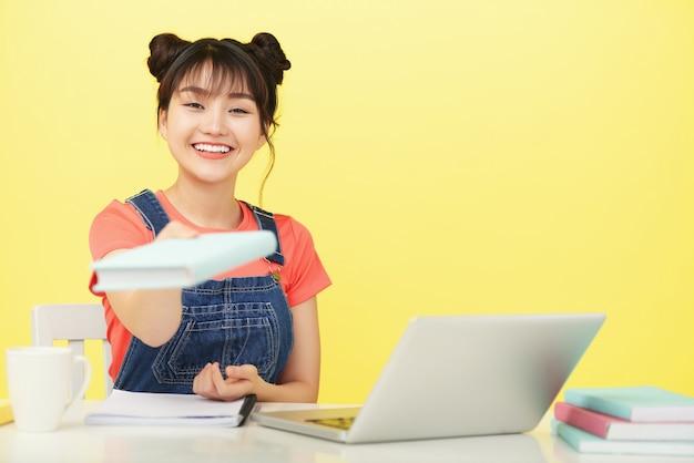 Sorridente giovane donna che dà libro