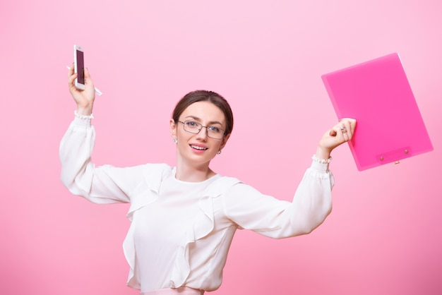 Una giovane donna sorridente con gli occhiali tiene in mano una cartella e un telefono cellulare