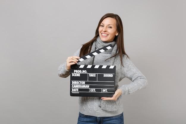 Sorridente giovane donna in maglione grigio, sciarpa tenere classico film nero ciak isolato su sfondo grigio. stile di vita sano, emozioni delle persone, concetto di stagione fredda. mock up copia spazio.