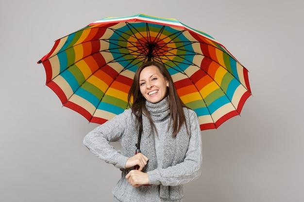 Sorridente giovane donna in maglione grigio, sciarpa azienda ombrello colorato isolato su sfondo grigio in studio. stile di vita sano, persone sincere emozioni, concetto di stagione fredda. mock up copia spazio.