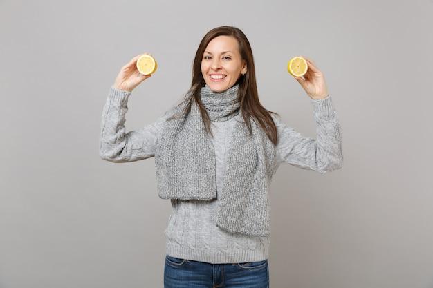 Sorridente giovane donna in maglione grigio, sciarpa azienda limoni isolati sul muro grigio sfondo ritratto in studio. stile di vita sano, persone sincere emozioni, concetto di stagione fredda. mock up copia spazio.
