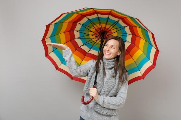 Sorridente giovane donna in maglione grigio, sciarpa che indica la mano che tiene ombrello colorato isolato su sfondo grigio muro. emozioni della gente di stile di vita sano di modo, concetto di stagione fredda. mock up copia spazio.