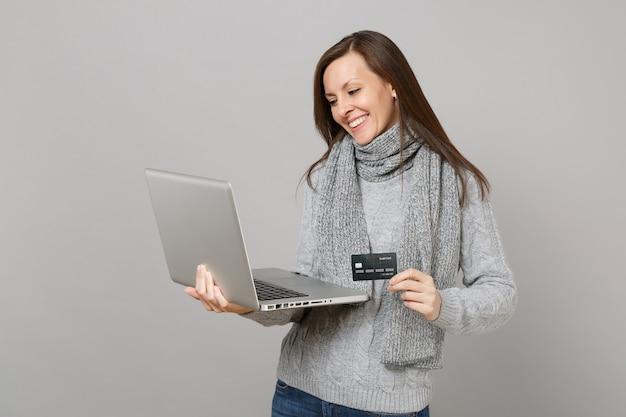Giovane donna sorridente in maglione grigio, sciarpa che lavora al computer del pc portatile che tiene la carta di credito bancaria isolata sul fondo grigio della parete. stile di vita sano, consulenza sul trattamento online, concetto di stagione fredda.
