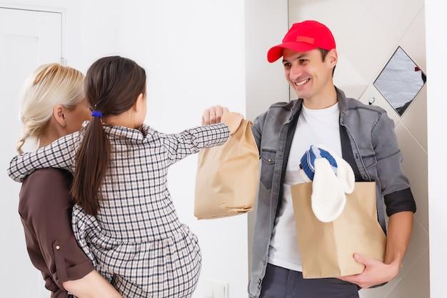 Sorridente giovane donna e sua figlia che ricevono la consegna di cibo dal fattorino a casa.