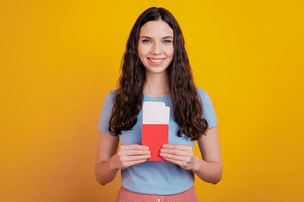 La giovane donna sorridente tiene la carta d'imbarco dei biglietti del passaporto isolata sul fondo della parete di colore giallo brillante