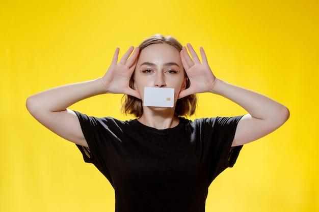 Sorridente giovane donna in possesso di carta di credito su sfondo giallo.