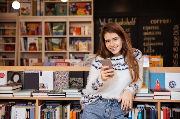 Sorridente giovane donna che tiene il telefono cellulare mentre è seduto in biblioteca