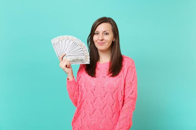 La giovane donna sorridente in maglione rosa lavorato a maglia tiene in mano un sacco di banconote in dollari, denaro contante isolato su sfondo blu muro, ritratto in studio. concetto di stile di vita della gente. mock up copia spazio.