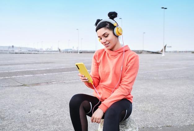 Sorridente giovane donna ascolta musica mentre utilizza il suo smartphone