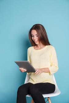 Sorridente giovane donna guardando il computer tablet pc isolato su sfondo blu