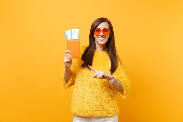 Sorridente giovane donna in occhiali cuore arancione puntando il dito indice sul passaporto e biglietti della carta d'imbarco isolati su sfondo giallo brillante. persone sincere emozioni, stile di vita. zona pubblicità.