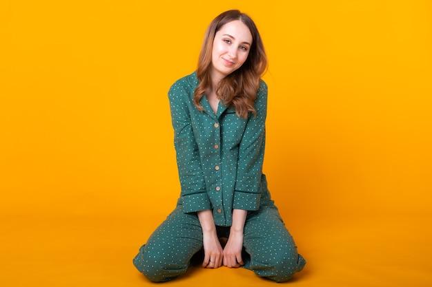 Sorridente giovane donna in pigiama casa indossare in posa mentre riposa a casa isolato sulla parete gialla