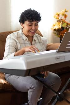 Una giovane donna sorridente che suona il pianoforte, seduta in un soggiorno