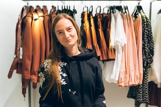 Sorridente giovane donna ritratto shopping vestiti alla moda