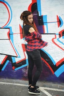 Ritratto di giovane donna sorridente con i dreadlocks, contro i graffiti