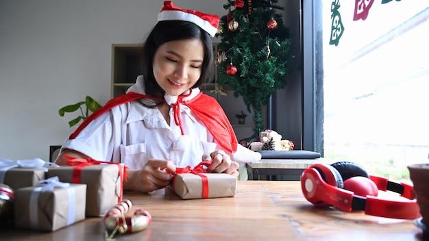 Sorridente giovane donna che si prepara per il natale e avvolge i regali a casa.
