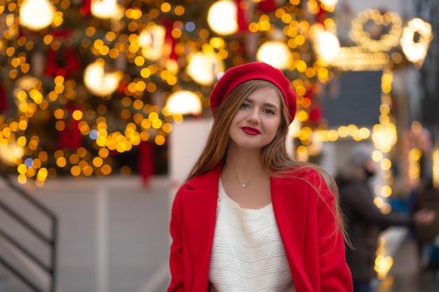 Sorridente giovane donna in cappotto rosso a piedi alla fiera di strada. spazio vuoto
