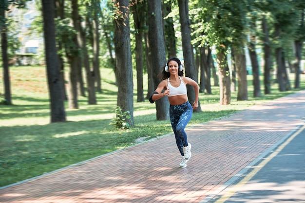 Sorridente giovane donna che corre in un parco cittadino