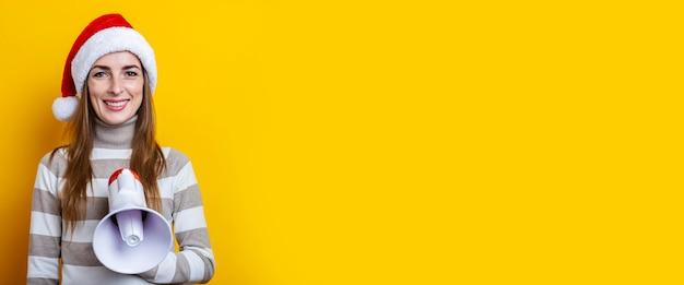 Sorridente giovane donna in cappello di babbo natale con un megafono su sfondo giallo. bandiera.