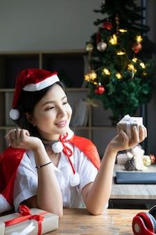 Sorridente giovane donna in cappello della santa che tiene i regali di natale.