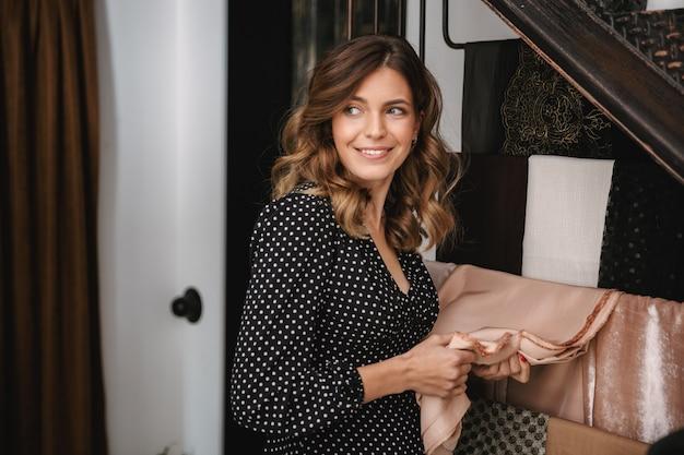Sorridente giovane donna sarta che lavora in officina, scegliendo tessile