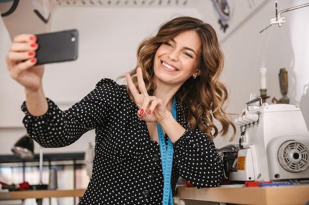 Sorridente giovane donna sarta che lavora in officina, utilizzando la macchina da cucire, prendendo un selfie