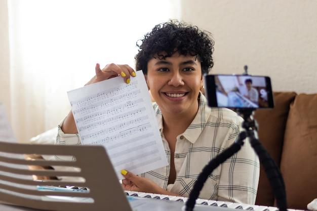 Una giovane donna sorridente che mostra uno spartito per pianoforte alla fotocamera di un telefono cellulare, seduta in un soggiorno