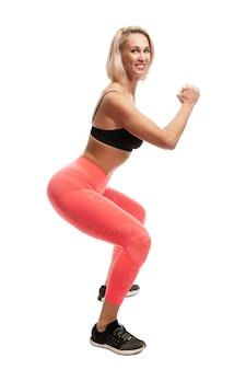 Sorridente giovane donna in abiti sportivi squat. isolato sulla parete bianca.