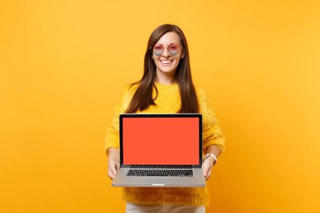 Sorridente giovane donna in maglione, occhiali cuore tenendo computer pc portatile con schermo vuoto nero vuoto isolato su sfondo giallo brillante. concetto di stile di vita di emozione sincera della gente. zona pubblicità.