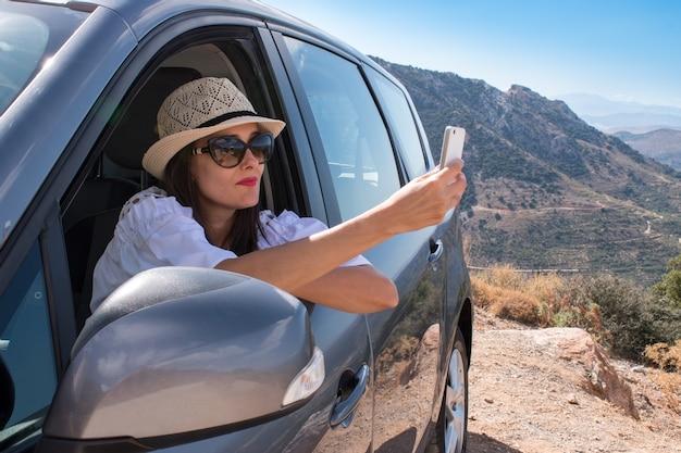 Sorridente giovane donna che scatta foto selfie con la fotocamera dello smartphone all'aperto in auto