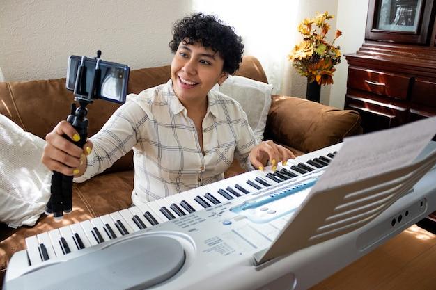 Una giovane donna sorridente che parla con la fotocamera di un cellulare, mentre suona il pianoforte, seduta in un soggiorno