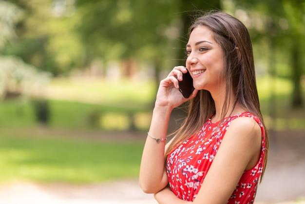 Giovane donna sorridente che parla sul telefono cellulare