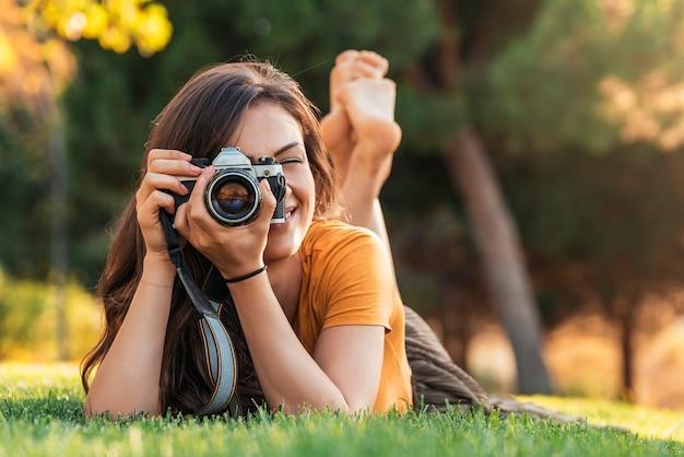 Sorridente giovane donna che utilizza una macchina fotografica per scattare foto al parco.
