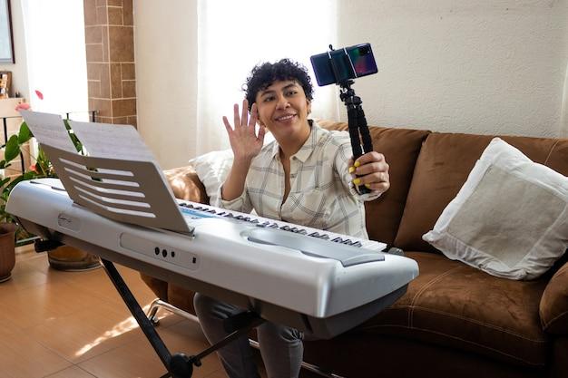 Una giovane donna sorridente che saluta la fotocamera di un cellulare, seduta davanti a un pianoforte in un soggiorno
