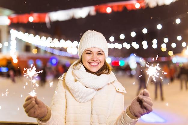 Sorridente giovane donna che indossa abiti invernali a maglia che tengono sparkler all'aperto su sfondo di neve