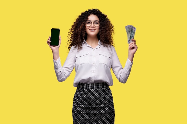 La giovane donna sorridente in camicia bianca tiene il telefono cellulare e ha vinto i soldi. la femmina gioca in un casinò online.